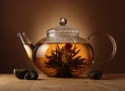 glass teapot with blooming herbal flower